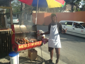 There are many people cooking up jerk chicken along the roads